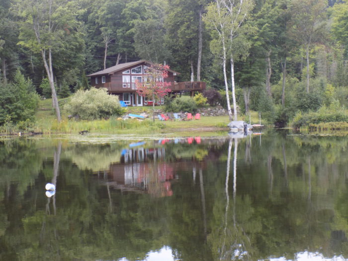 House across the lake at Riverbank Cottages & Trailers
