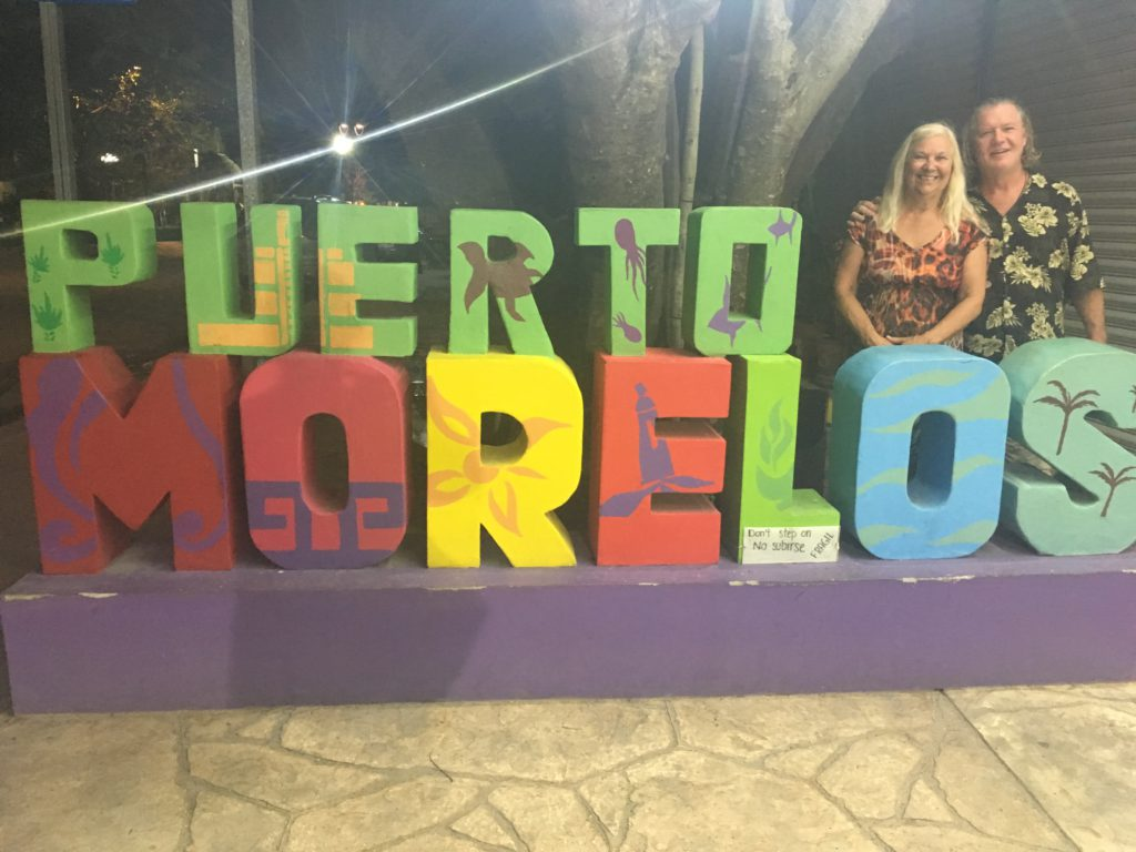 two people standing by a sign in Puerto Morelos, Mexico