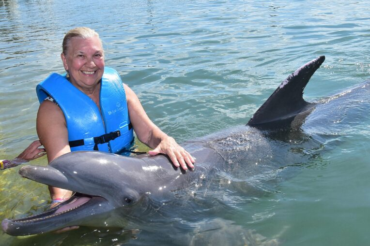 Woman patting a dolphin